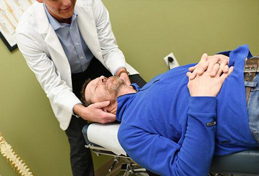 Chiropractor adjusting patient.